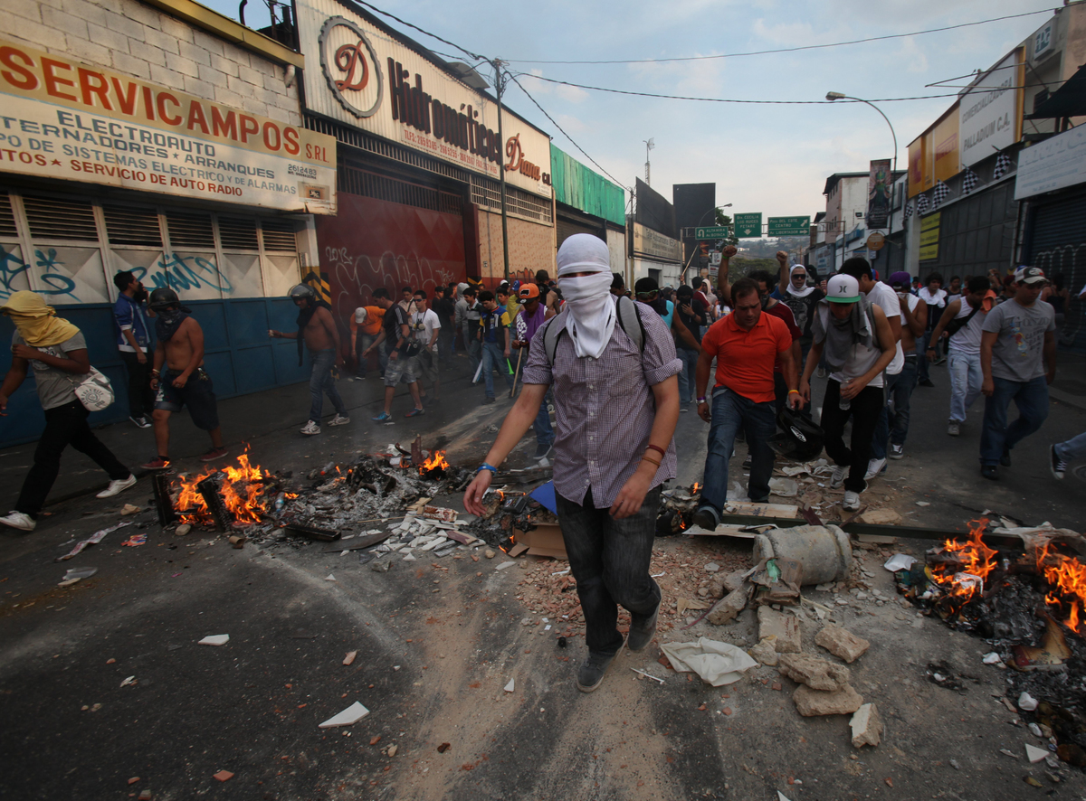 Opposition supporters and students cross a barricade during clashes with riot police in Caracas, Venezuela, Monday, April 15,