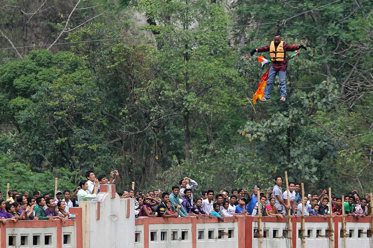 Indian stuntman Sailendra Nath Roy is watched by onlookers as he hangs on a rope while attempting to cross the River Teesta o