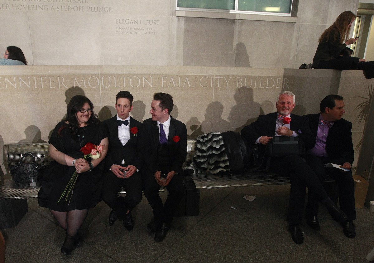 After midnight, Briceson Ducharme, second from left, sits with his partner Aaron Buck, center right, as they await their turn