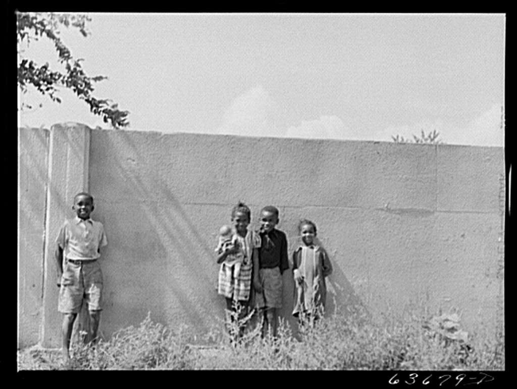 In this 1941 photo supplied by the United States Library of Congress, children are shown standing in front of half mile concr
