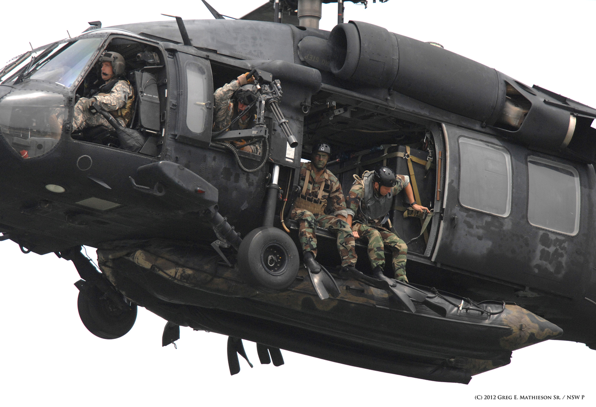 SEALs sit ready in the doorways with their Zodiac suspended below at US Army  HH-60H Seahawk belonging to the 160th Special O