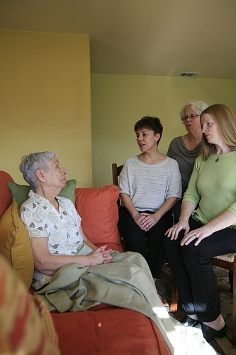 Threshold Choir singers Theresa Fischer, Pat Friday and Joanne Conklin rehearse singing to a choir member last spring in Napa