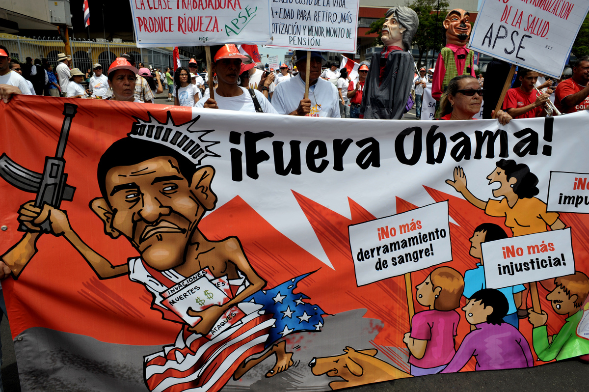 Demonstrators hold a banner against the upcoming visit of US President Barack Obama during a May Day rally in San Jose on May