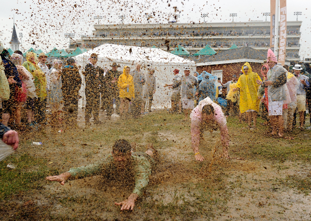 LOUISVILLE, KY - MAY 04:  Fans slide through the mud in the infield prior to the 139th running of the Kentucky Derby at Churc