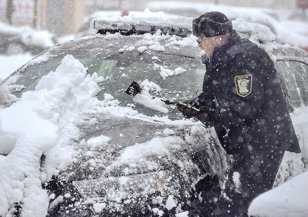 Austin Police's Sgt. Joe Milli clears heavy snow off his police cruiser Thursday morning, May 2, 2013 behind the Law Enforcem
