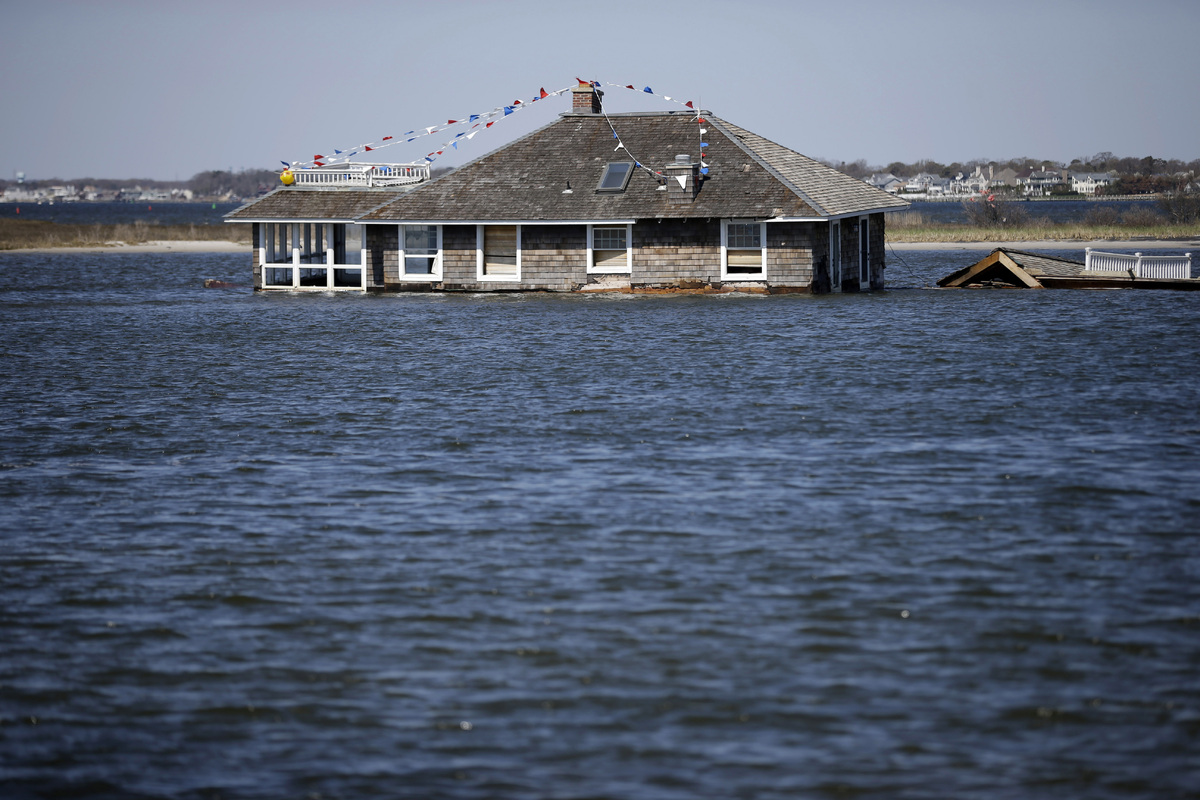 FILE - In this file photo of April 25, 2013, a home rests in Barnegat Bay, in Mantoloking, N.J., where it was swept to by Sup