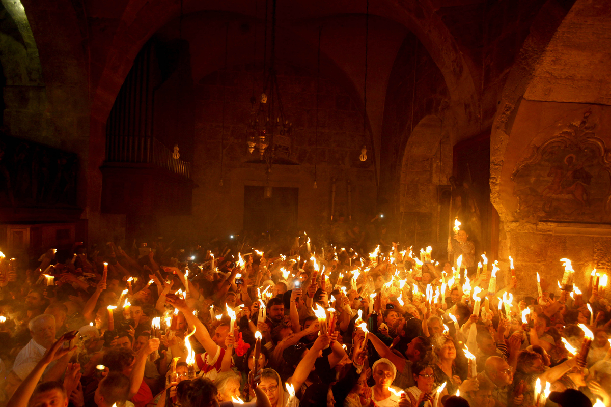 Christian Orthodox worshippers hold up candles lit from the 'Holy Fire' as thousands gather in the Church of the Holy Sepulch