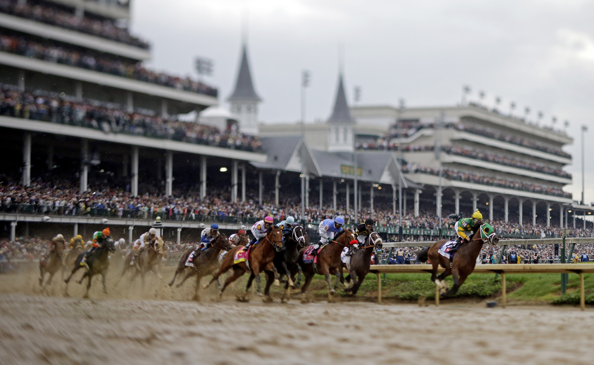 Horses make their way around turn one during the 139th Kentucky Derby at Churchill Downs Saturday, May 4, 2013, in Louisville