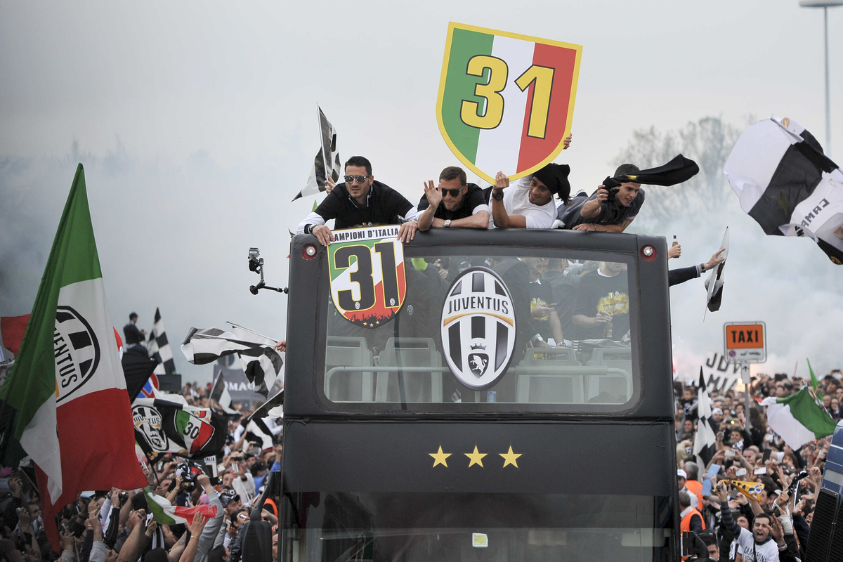 Juventus players are celebrated by supporters as they tour Turin, Italy, on a coach after they defeated Palermo 1-0 to win th