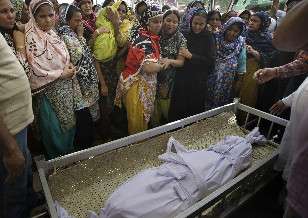 Pakistani Women mourn next to the body of a child, who killed in the Saturday's bombing, during a funeral in Karachi, Pakista