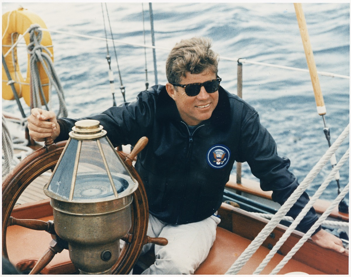 "President Kennedy vacations in Maine at the wheel of the U.S. Coast Guard yacht ""Manitou"" in Boothbay Harbor, Maine on August"
