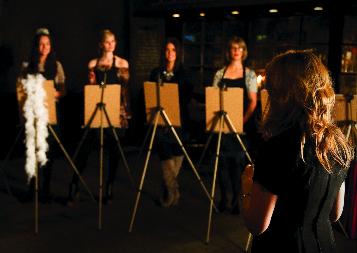 The students stand at their easels.
