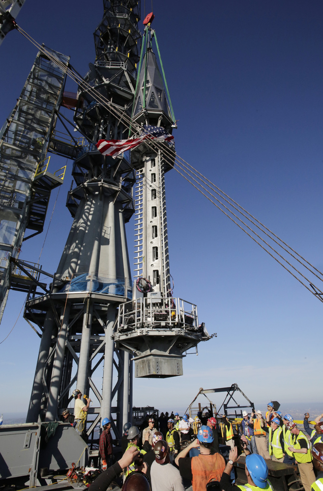 The final piece of spire is hoisted in place on top of One World Trade Center, Friday, May 10, 2013 in New York. The addition