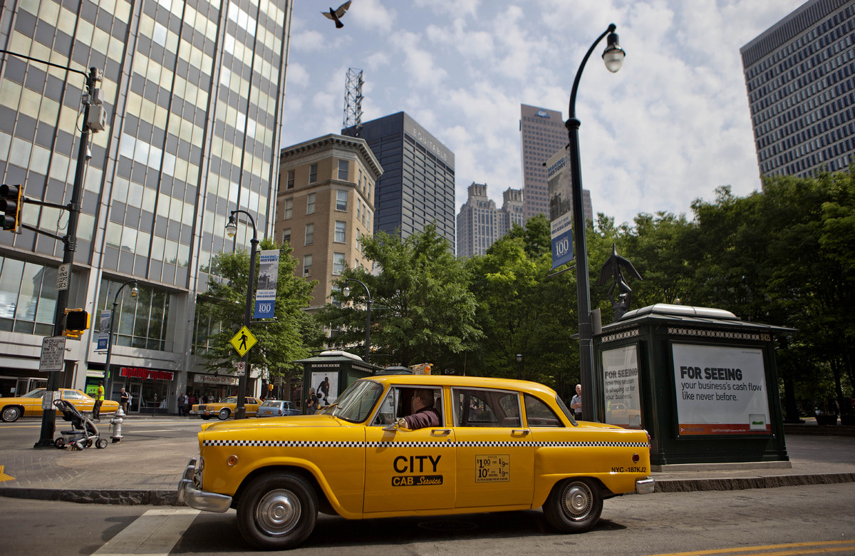 A vintage New York City checker cab waits to be driven through downtown Peachtree Street as the area is turned into the set f