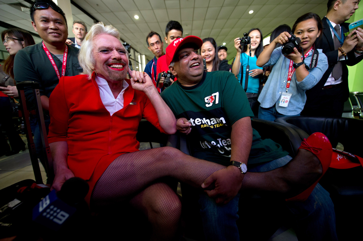 British billionaire Richard Branson (L) shares a light moment with AirAsia group chief Tony Fernandes (C) at the Low Cost Car