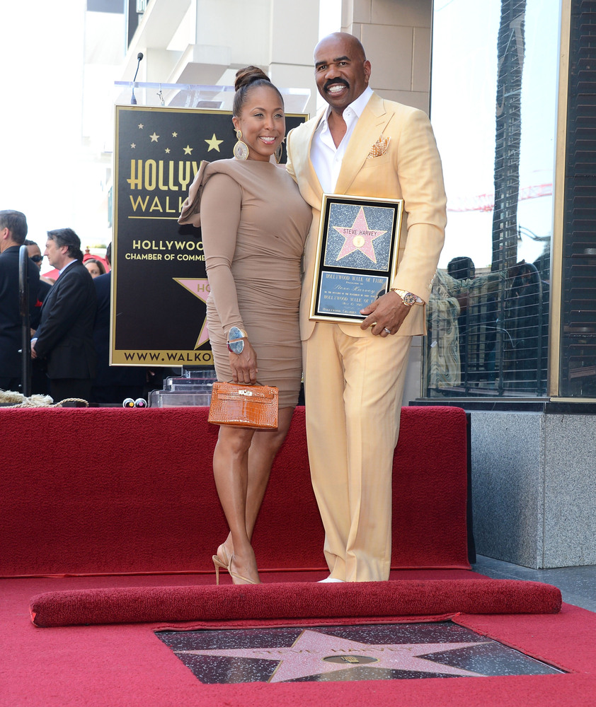 HOLLYWOOD, CA - MAY 13:  Actor and radio host Steve Harvey (R) poses on his star on the Hollywood Walk of Fame with his wife