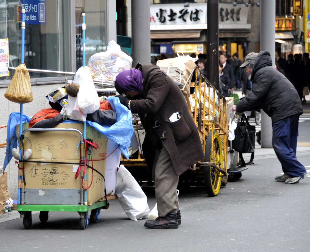 A poor Japanese man pushes a cart in downtown Tokyo on March 2, 2010.  (YOSHIKAZU TSUNO/AFP/Getty Images)