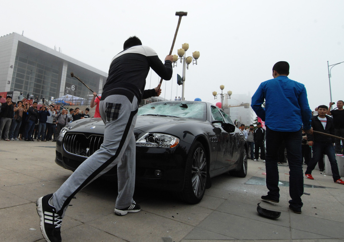 A Maserati Quattroporte is smashed with sledge hammers during the opening ceremony of the Qingdao Internationall Auto Show on