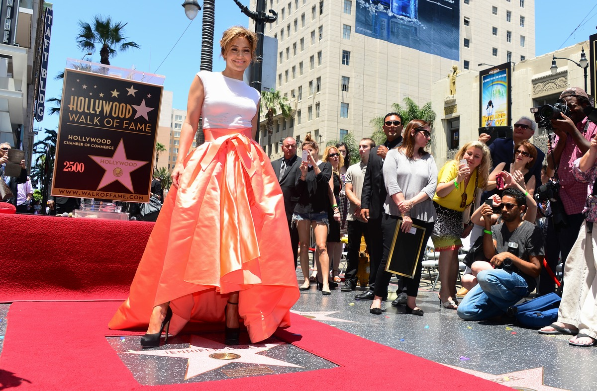 International superstar Jennifer Lopez poses while stepping on her just unveiled star in Hollywood, California, on June 20, 2