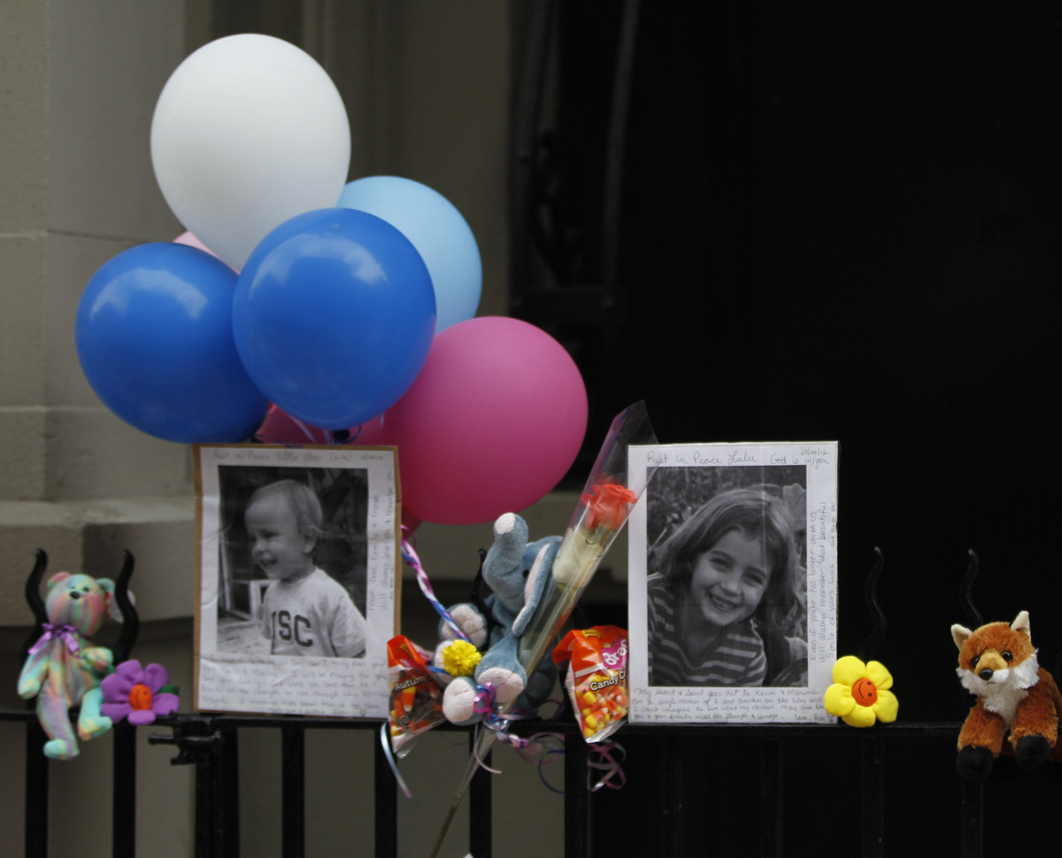 FILE - In this Oct. 27, 2012 file photo, Photographs of the two children allegedly stabbed by their nanny are displayed along