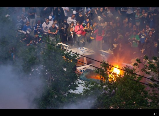 Rioters burn police cars after the Vancouver Canucks were defeated by the Boston Bruins in the NHL's Stanley Cup Final in Van