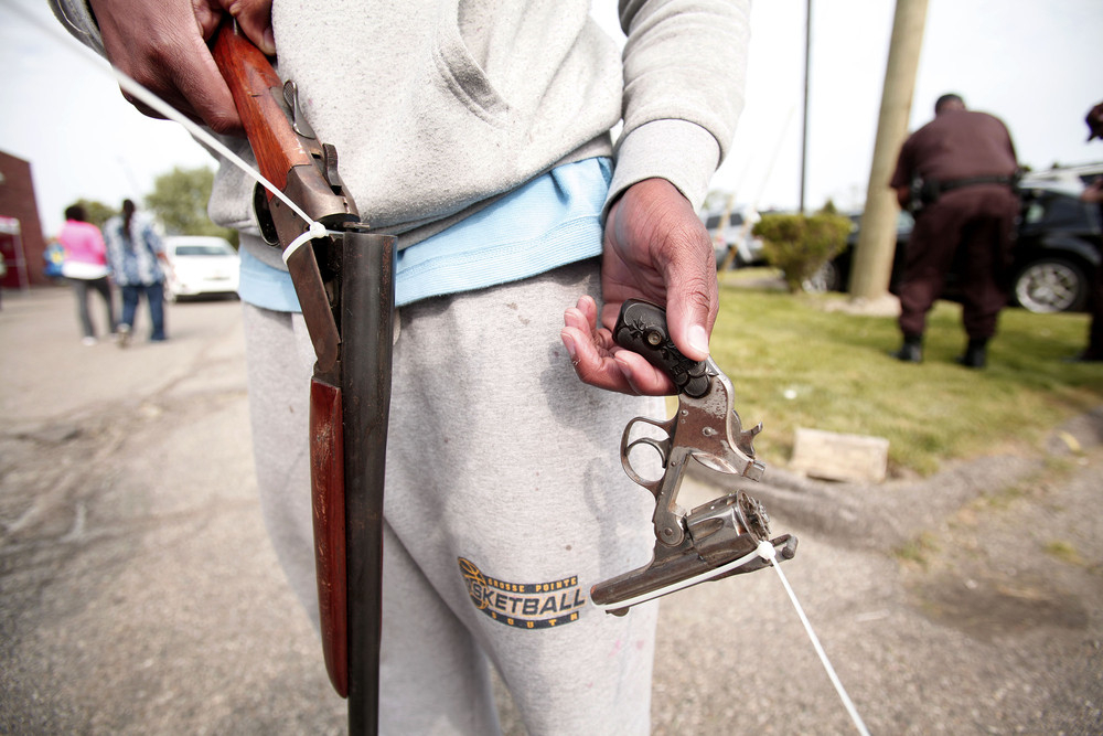 A man displays two guns he is bringing in to exchange for two $50 Meijer gift cards at a 'Groceries For Guns' gun buyback pro