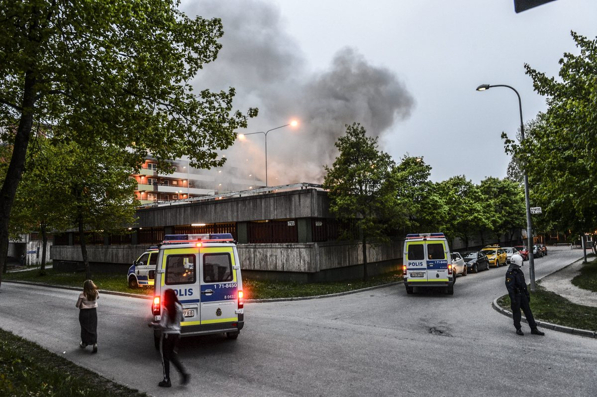 Policemen secure an apartment building after youths rioted in Husby, northern Stockholm on May 20, 2013. Youths in the immigr