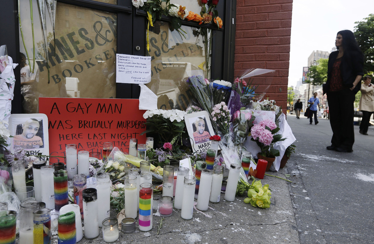 Pedestrians pass a makeshift memorial for 32-year-old Mark Carson, Monday, May 20, 2013, in New York. Police said Elliot Mora