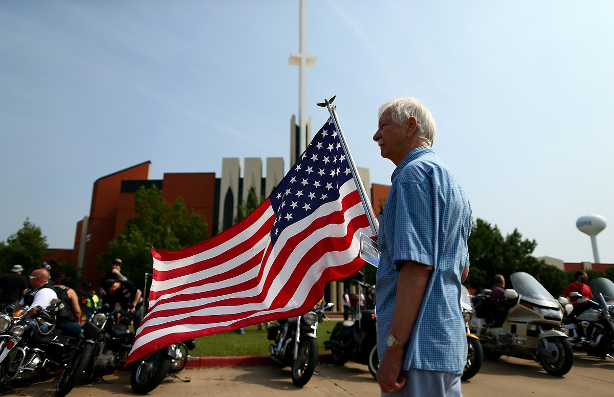 MOORE, OK - MAY 24:  Larry Cory displays an American flag outside the funeral for nine-year-old tornado victim Nicholas McCab