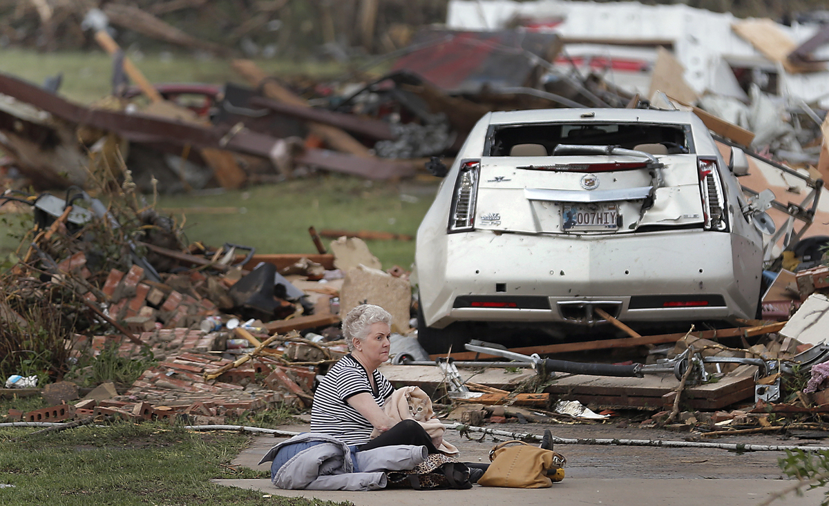 Kay James holds her cat as she sits in her driveway after her home was destroyed by the tornado that hit the area on Monday,