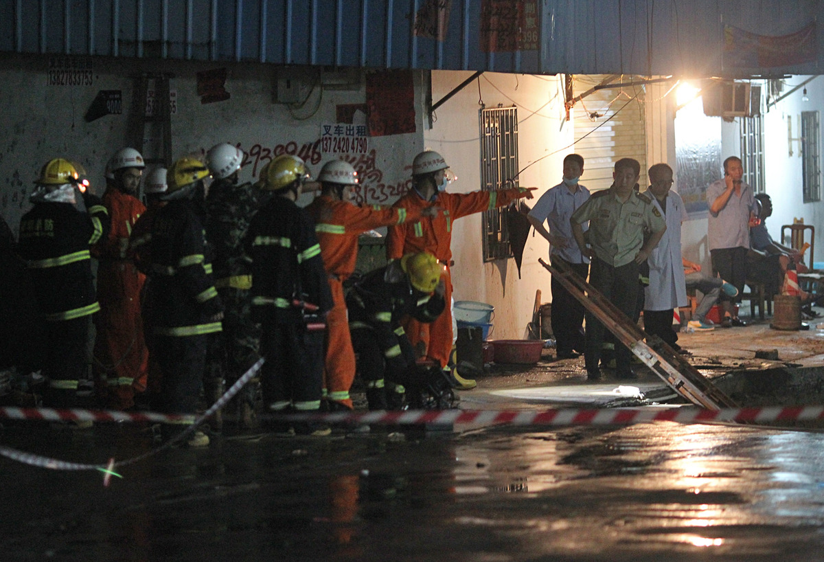 Rescuers search for people buried in a road cave-in accident site on May 21, 2013 in Shenzhen, China. (ChinaFotoPress/ChinaFo