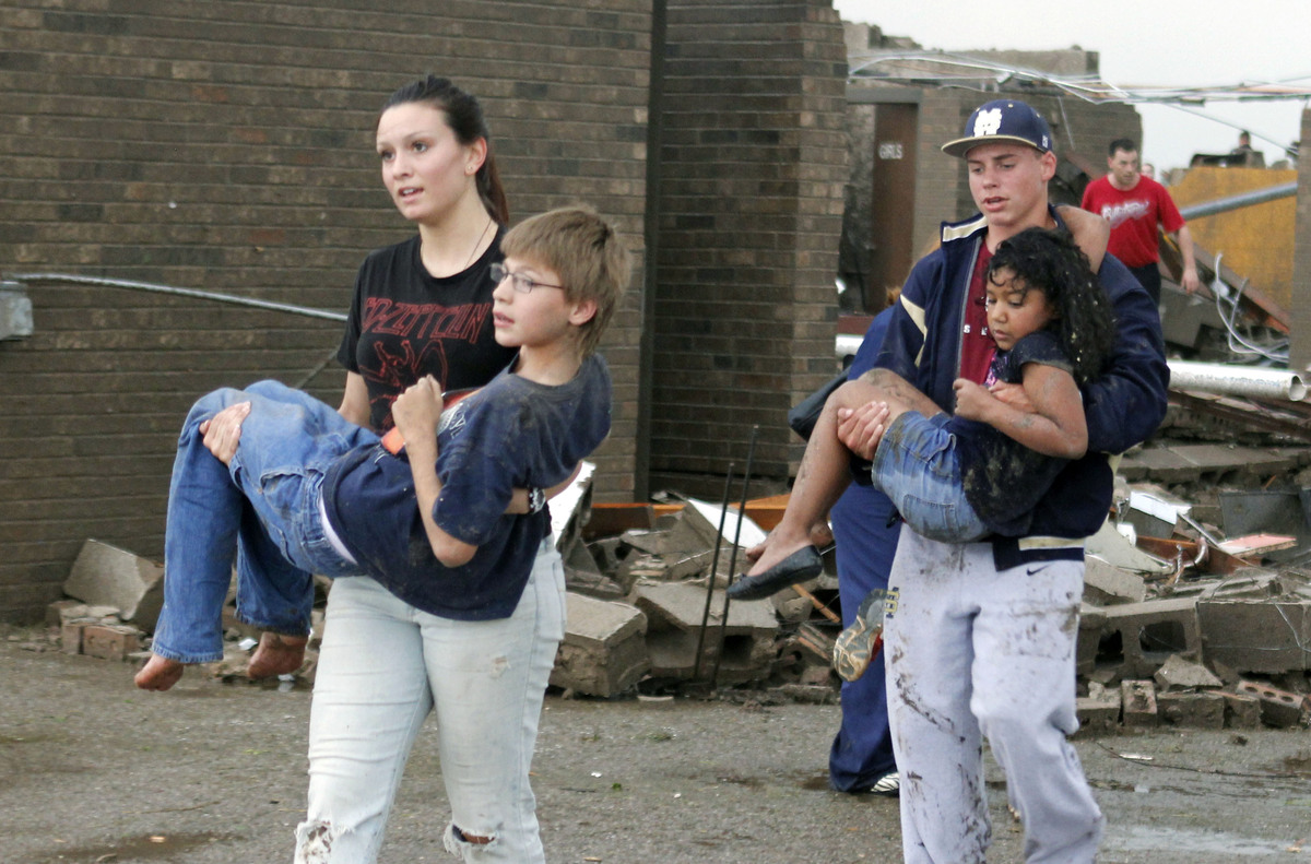 Teachers carry children away from Briarwood Elementary school after a tornado destroyed the school in south Oklahoma City, Ok