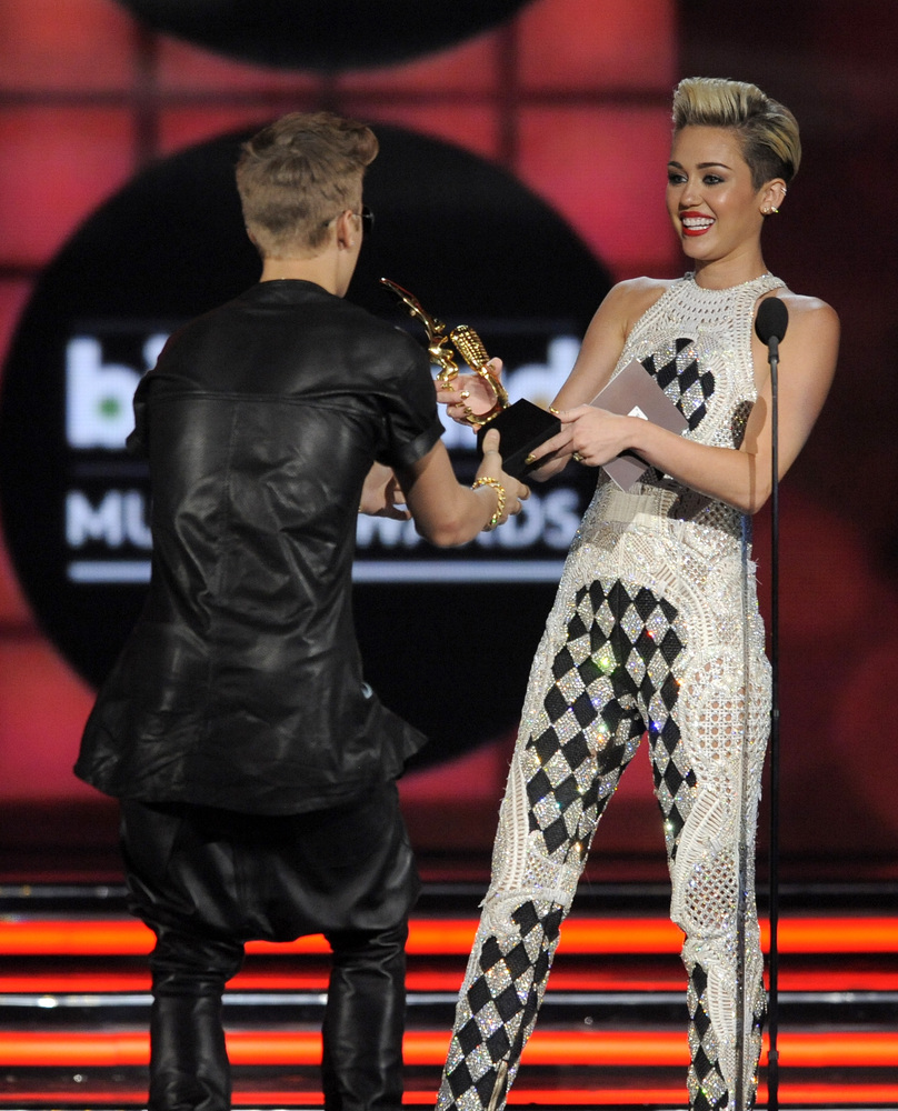 Miley Cyrus, right, presents the award for top male artist to Justin Bieber at the Billboard Music Awards at the MGM Grand Ga