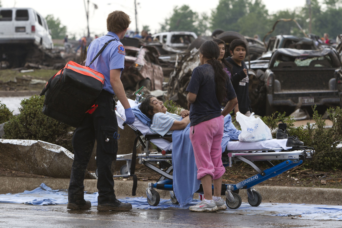 A Moore Medical Center patient sits in the parking lot after a tornado damaged the hospital in Moore, Okla., on Monday, May 2