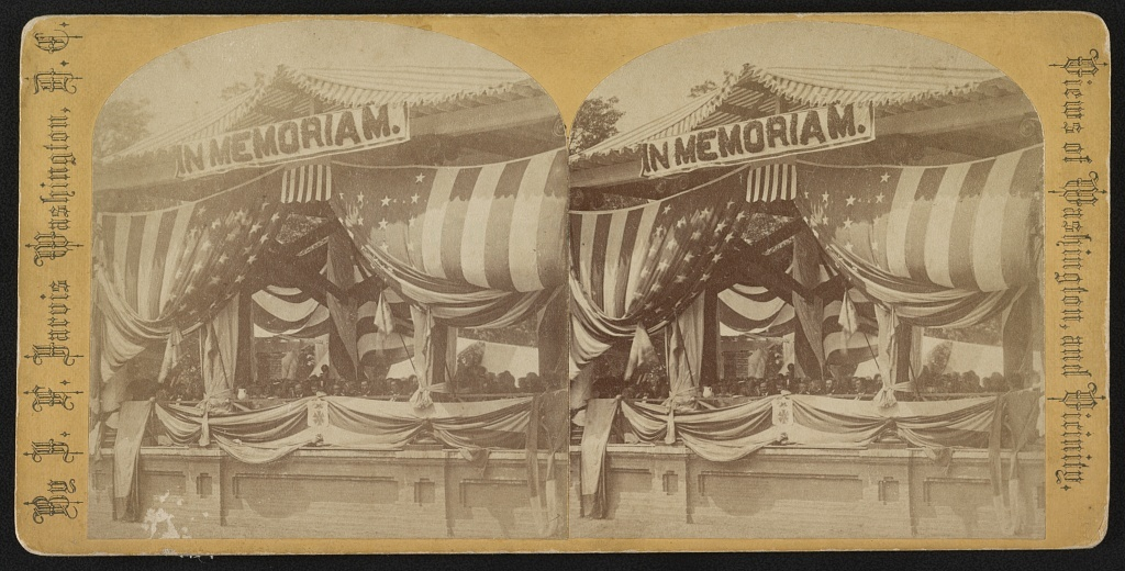Stereograph shows President Ulysses Grant and General John Logan seated at flag-draped reviewing stand. At the time Grant was