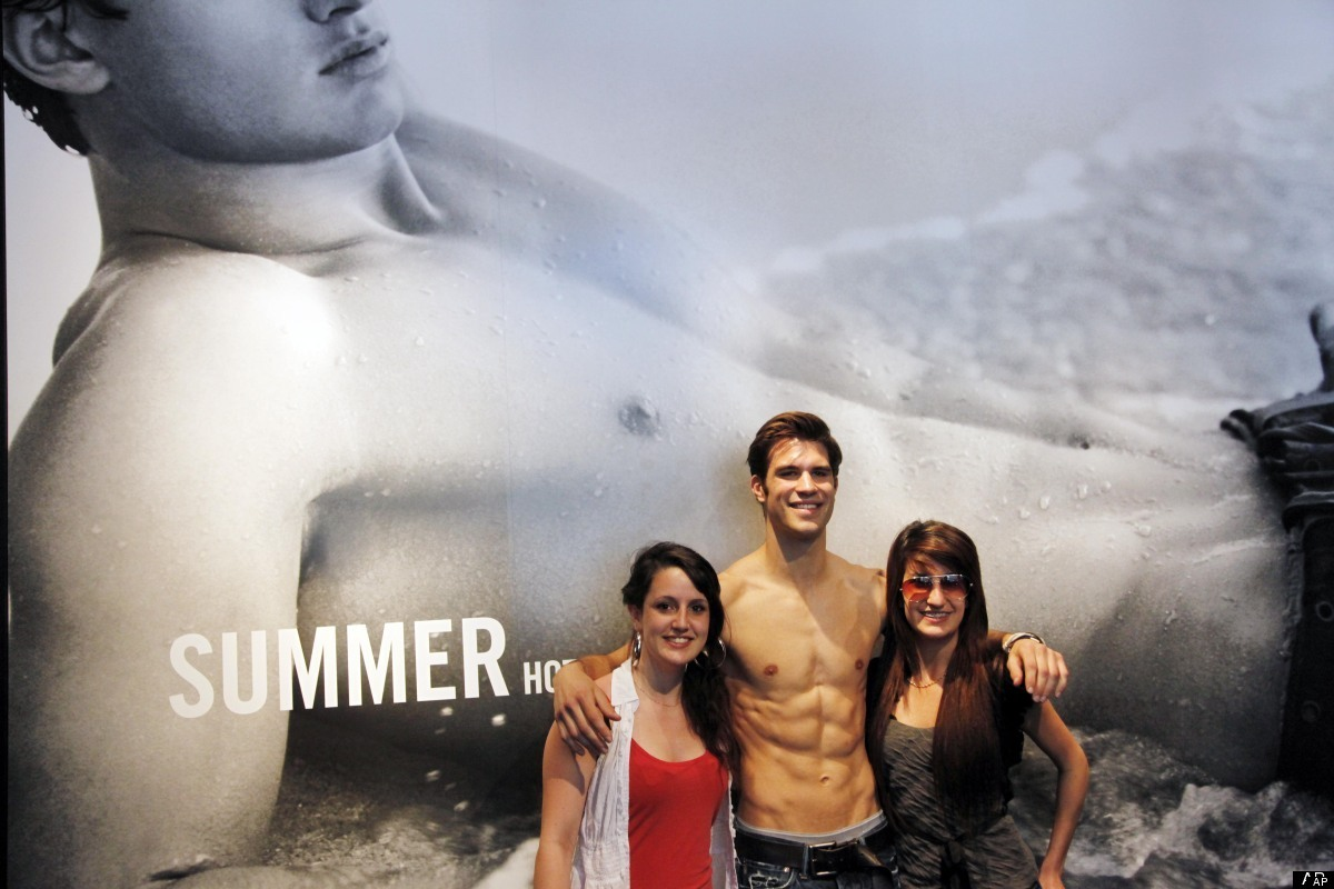 In this May 25, 2011, a well-toned Abercrombie & Fitch employee, center, poses for photos with two customers at the entrance