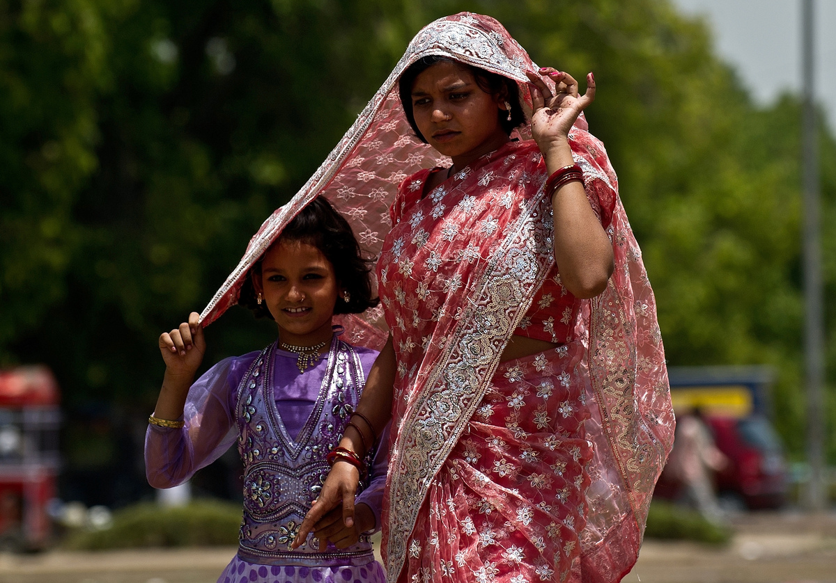 An Indian woman shields a child's head with her sari to provide shade from the sun in New Delhi on May 23, 2013. Heatwave con
