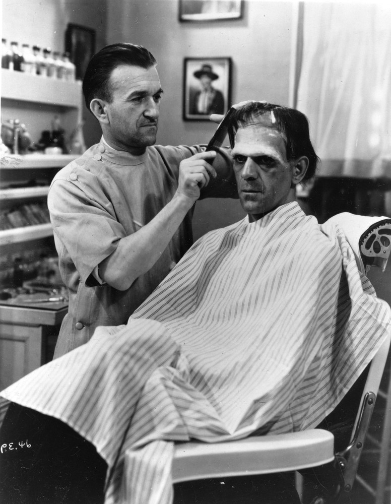Make-up artist Jack P. Pierce applies make-up and combs the hair of British actor Boris Karloff (1887 - 1979) for Karloff's r