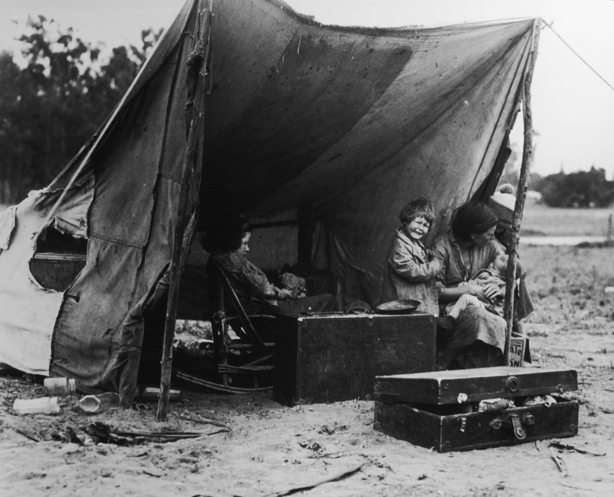 A migrant mother sits in her camp while her children play - photographed by Dorothea Lange - in Nipomo, California, USA, 1936