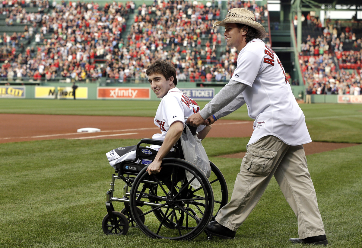 Boston Marathon bombing survivor Jeff Bauman, left, is wheeled out by Carlos Arredondo, the man who helped save his life, to