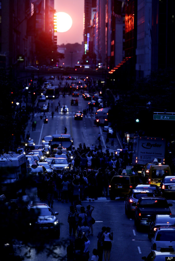 People stand in the middle of 42nd Street in New York's Manhattan borough as the sun sets through the middle of the buildings