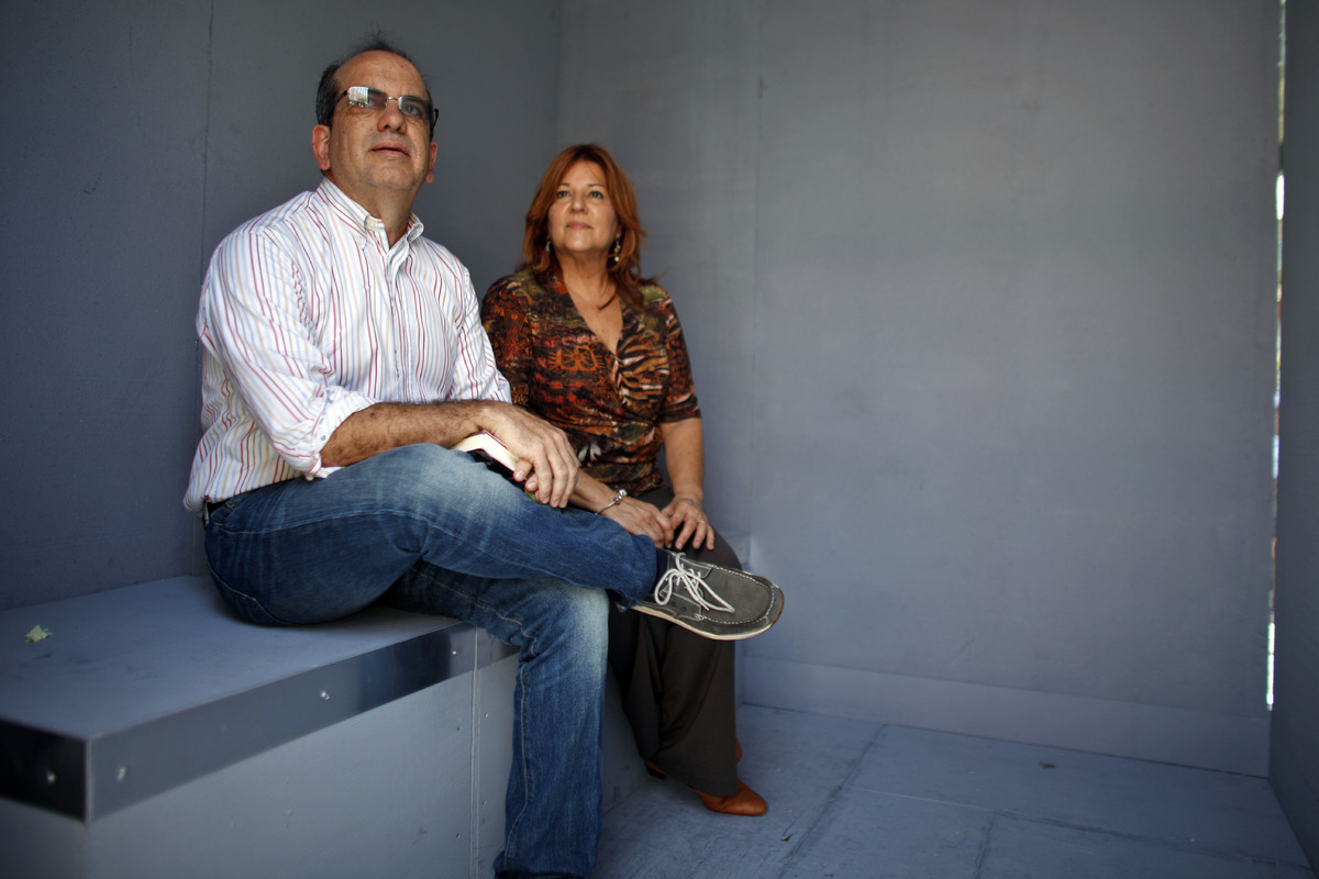 Former Puerto Rico Governor Anibal Acevedo Vila and wife Senator Luisa Gandara sit inside a mock cell during a protest demand