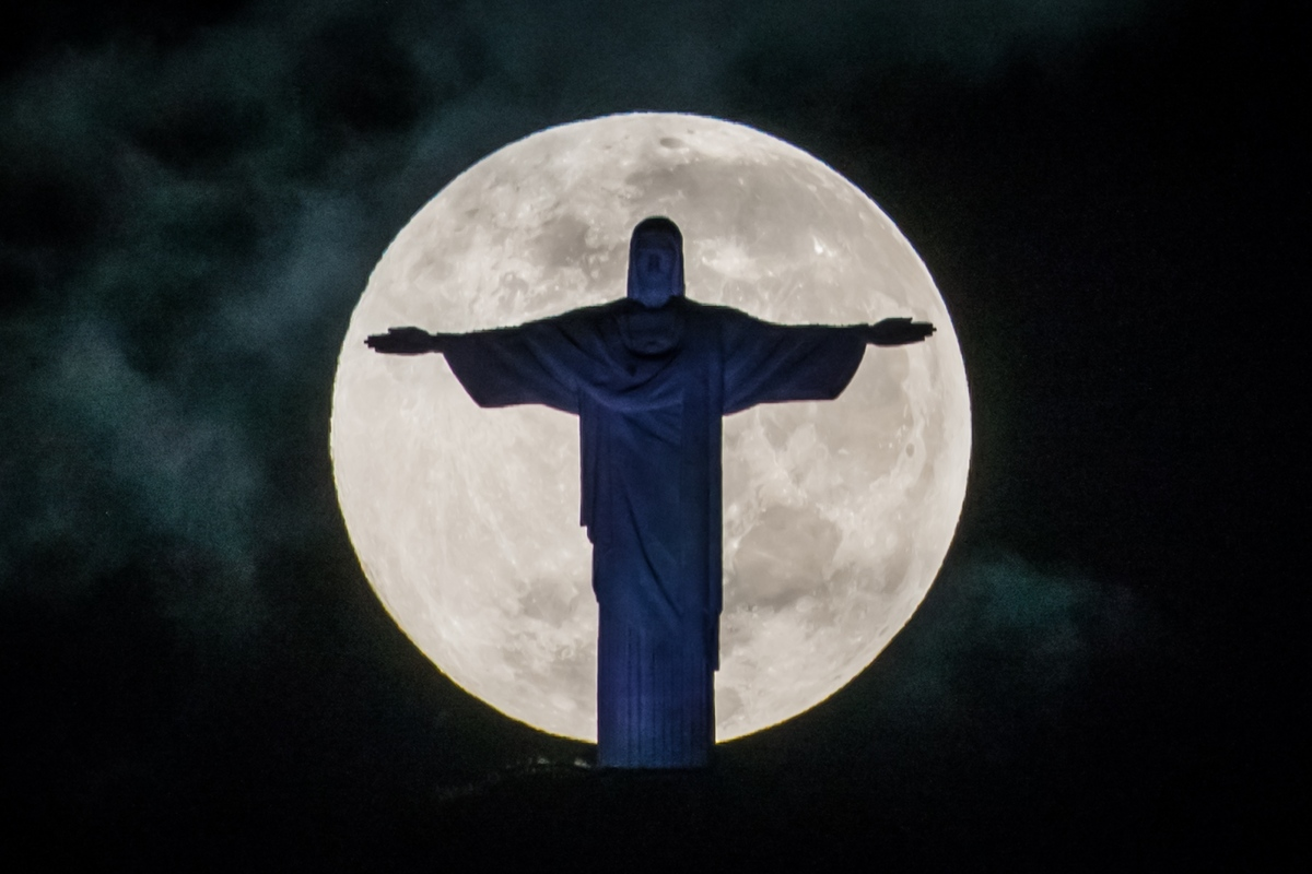 A full moon sets behind the Christ the Redeemer statue on top of Corcovado hill in Rio de Janeiro, Brazil, on May 25, 2013. (
