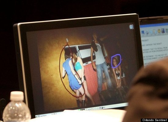 """Prosecutors look at a photo entered into evidence of Casey Anthony, in the the blue dress, dancing at a """"hot body"""" contest in"""