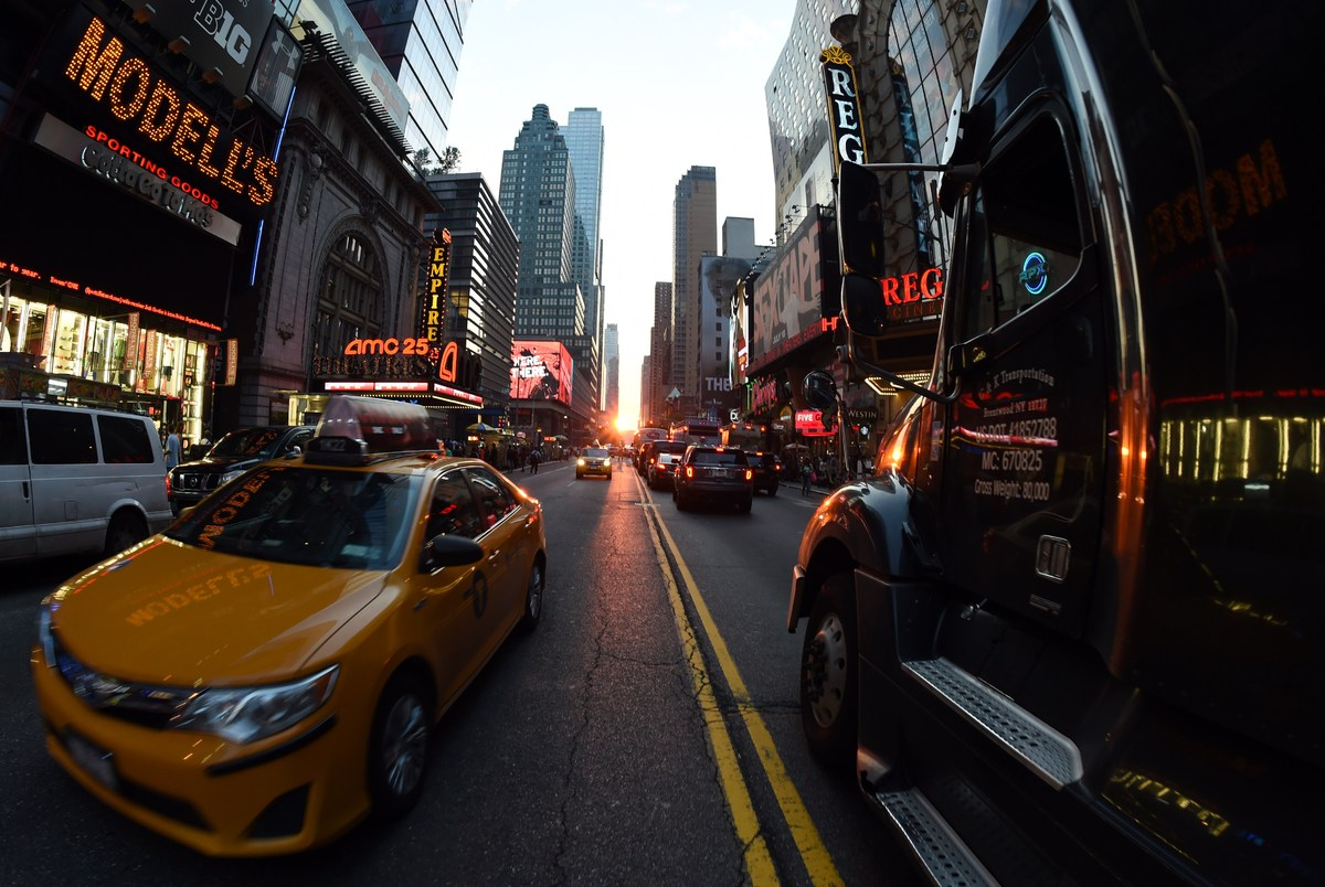 Traffic slows as tourists and pedestrians watch the Manhattanhenge phenomenon July 11, 2014 on 42nd Street in New York. The e