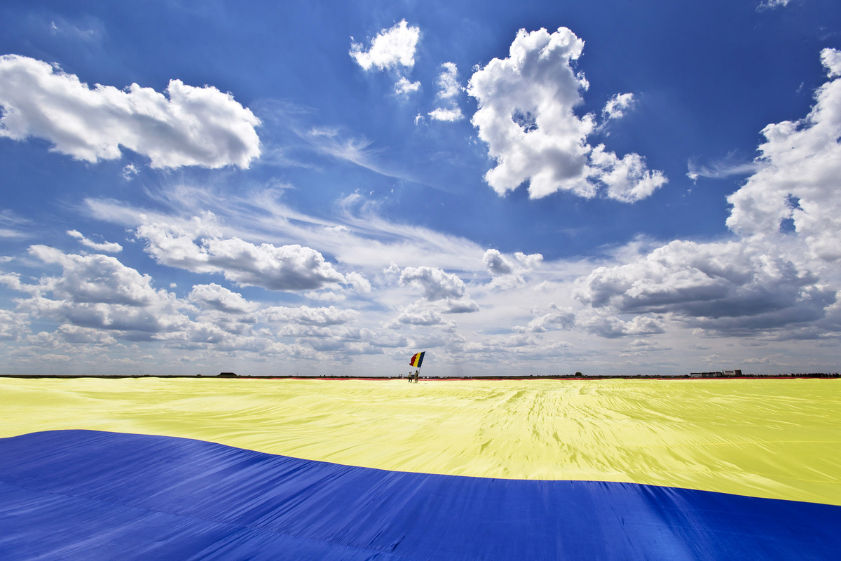 A man holding a Romanian flag stands on a record breaking version of the flag, on the Clinceni Airfield, south of Bucharest,