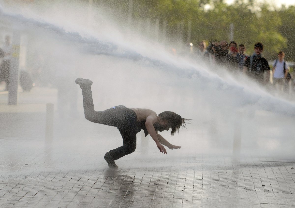 A man falls as riot police use tear gas and pressurized water to quash a peaceful demonstration by hundreds of people staging