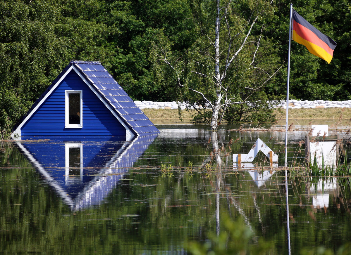 The roof of a summer cottage mirrors in the flooded area near Doemitz at the river Elbe, northern Germany, Monday June 10, 20