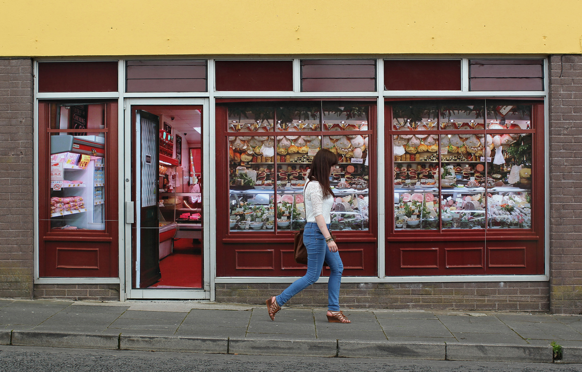 A pedestrian walks pass stickers applied to the windows of a former butcher's shop in Belcoo, Northern Ireland, outside Ennis