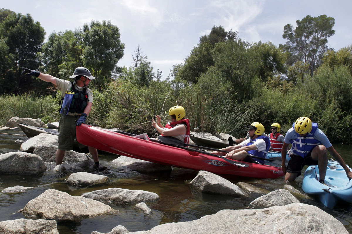 This Aug. 12, 2011 photo shows Ranger Tim Pera, left, with the Santa Monica Mountains Recreation Conservation Authority, help
